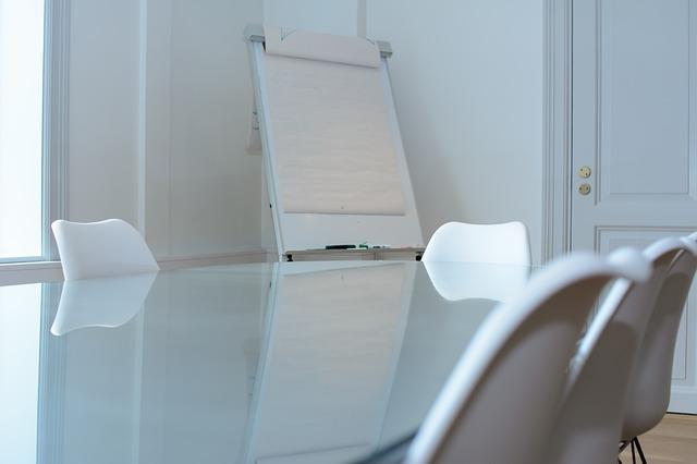 Ein kleiner, in weiß gehaltener Seminarraum mit Tisch, 5 Stühlen und einem Flipchart